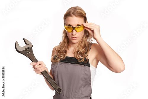 Leinwanddruck Bild Junge Frau mit grossen Schraubenschluessel