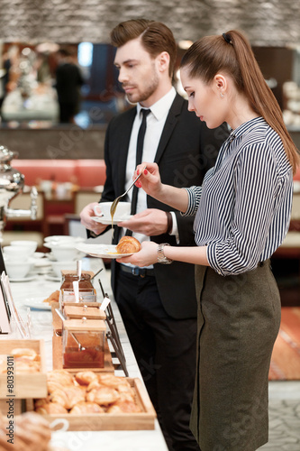 Business managers take croissants and jam at the buffet - 80393011