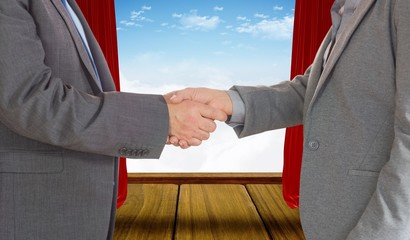 Composite image of close up on two businesspeople shaking hands