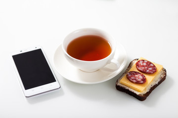 White smartphone,  a cup of tea and sandwich on white glass tabl