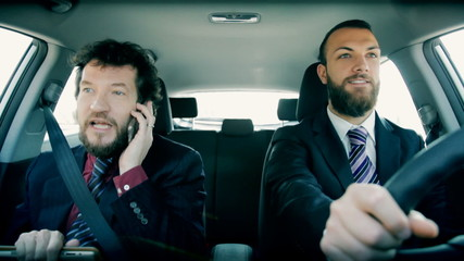 Two business men working in car on the phone driving
