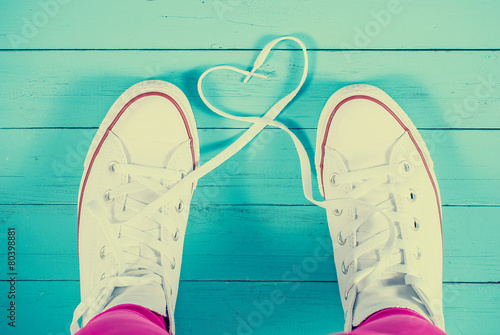 Leinwanddruck Bild Sneakers with heart on blue wood background, filtered image
