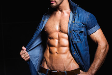 Muscular and sexy body of young hunk in jeans shirt