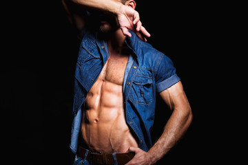 Muscular and sexy body of young man posing in jeans shirt