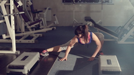 Brunette doing stretching in a fitness room among exercise