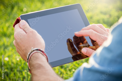Tuinposter Ontspanning Adult man using a digital tablet at the park