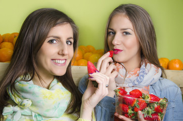 Two beautiful young girls eating strawberries from punnet