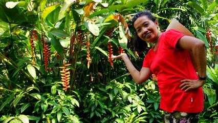 fröhliche Asiatin posiert vor tropischem Hintergrund