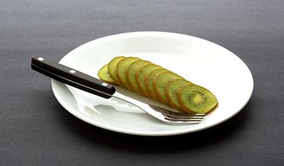 Sliced kiwi fruit on plate with fork