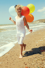 little girl runs along the coastline with balloons