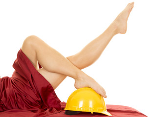 woman legs with red sheet on foot on construction hat