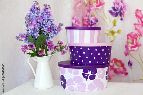Foto op Canvas Lilac A vase with a bouquet of lilac and gift boxes