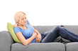 Blond woman feeling stomach pain seated on a gray sofa