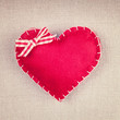 Red heart with a bow on vintage fabric background