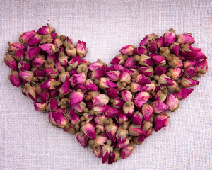 Shape of a heart made out of dried pink roses on fabric backgrou