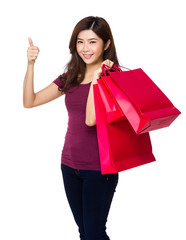 Happy shopping young woman show thumb up with bags