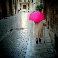 Anciana con paraguas caminando con bastón