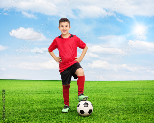Cheerful youngster standing over a football on field