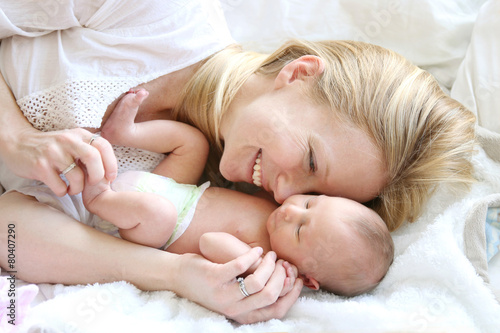 Happy Young Mother Snuggling Newborn Baby Daughter in Bed - 80407290