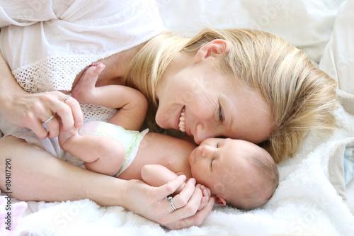 Leinwanddruck Bild Happy Young Mother Snuggling Newborn Baby Daughter in Bed
