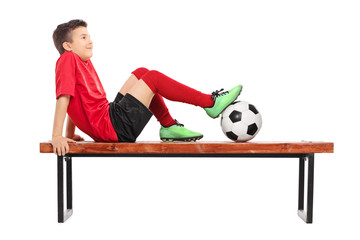 Pensive junior football player sitting on a bench