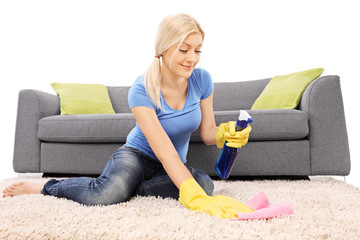 Woman cleaning a carpet with a cleaning spray