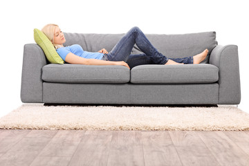 Young blond woman taking a nap on a sofa