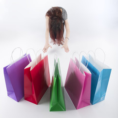 Woman Bowing on Floor In Front of Shopping Bags
