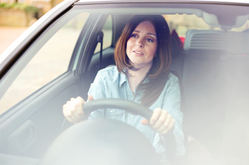 young woman driving her car looking anxious