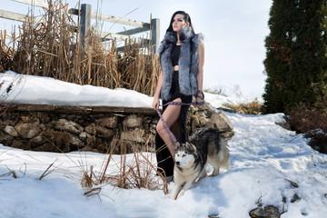 Elegant girl in a fur vest with the Laika dog