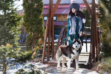 Serious woman in a fur hat with a Husky dog