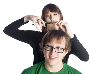 Female hair stylist cutting hair of a worried man
