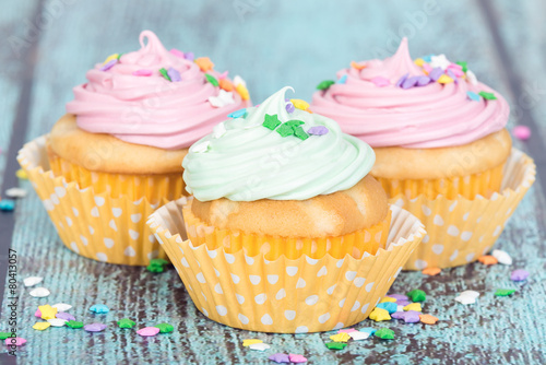 Papiers peints Dessert Pastel cupcakes with sprinkles on blue vintage background