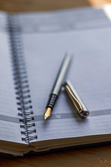 Closeup photo of open notebook with a fountain pen