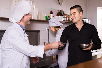 Male waiter holding dishes at kitchen