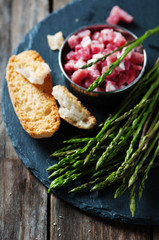 Asparagus with ham on the wooden table, selective focus