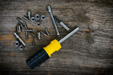 Screwdriver and bits on a textured wood background
