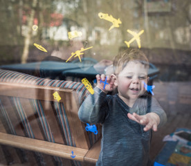 boy laughing behind window with stickers