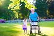 Leinwanddruck Bild - Grandmother with walker and little girl in a park