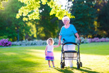 Grandmother with walker and little girl in a park