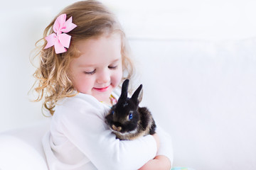 Happy little girl playing with a rabbit