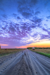 Sunset over rural road and hay bales