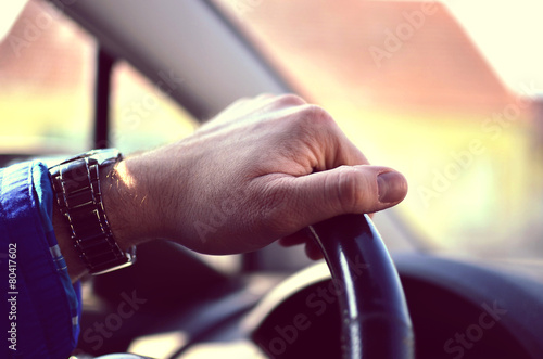 Driver hands holding steering wheel - 80417602