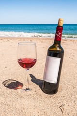 A bottle of wine and glass on the beach