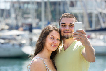 Girl and guy taking selfie in city