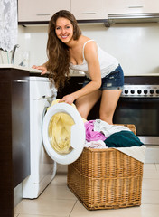 Nice woman with clothes near washing machine