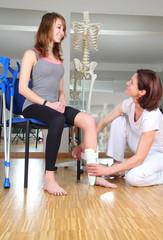 Physiotherapeutin bei Patientin mit Fußverletzung