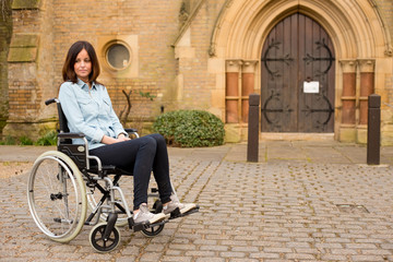 a sad young woman in a wheelchair waiting outside a church