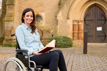wheelchair user holding a bible