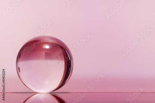 Glass transparent ball on light pink background and mirror - 80422224